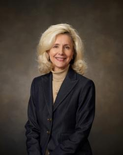 A studio portrait of Dr. Sarah Clemmons, president of Chipola College. She is blonde, posing with her hands crossed in front, wearing a turtleneck and blazer.