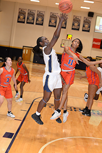A Chipola basketball player goes up for a rebound in the midst of opposing players.