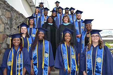 SSS Students pose in their cap and gowns at Graduation
